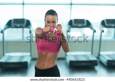 Muscular Boxer Woman MMA Fighter Practice Her Skills With Dumbbells In A Gym - Athletic Bodybuilder Fitness Model - stock photo