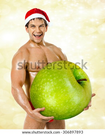 muscular  bronzed handsome sexy Santa Claus on white  background, hold great green apple and laughing - stock photo
