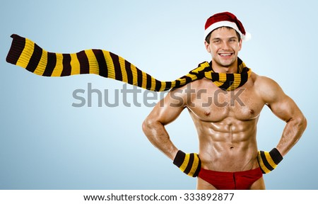 muscular bronzed hfitness Santa Claus; in muffler on blue  background,  smile - stock photo