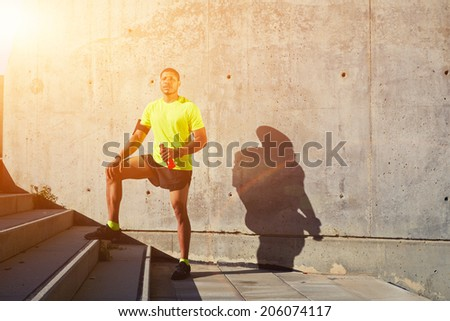 Muscular build sportsman holding bottle of water in the hand,  athletic male runner resting after training, attractive sporty man taking break after evening run, fitness and healthy lifestyle concept - stock photo