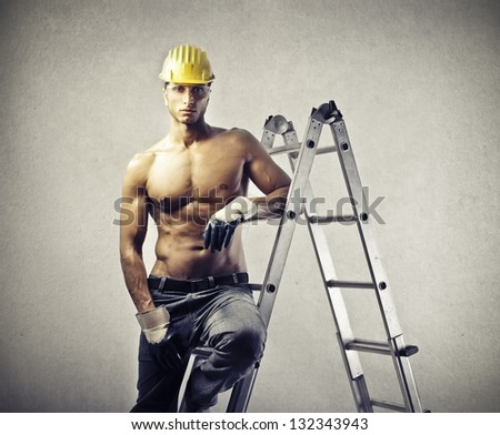 muscular builder with helmet and ladder - stock photo