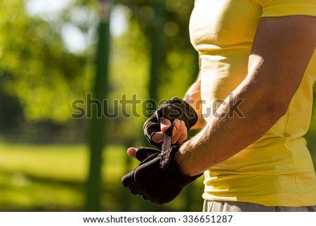 Muscular built young athlete working out in an outdoor gym, puts on sports gloves before training - stock photo