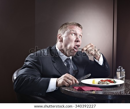 Muscular businessman eating and lick the plate - stock photo