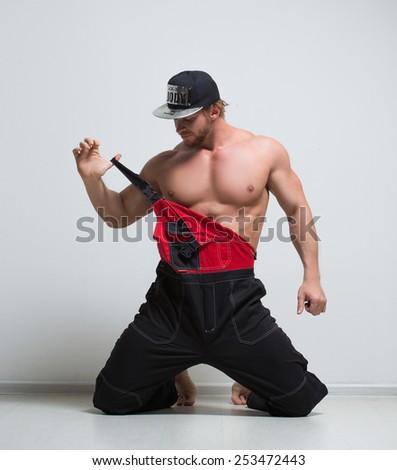 muscular construction worker in overalls. kneeling - stock photo