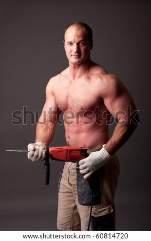 muscular construction worker with drill - stock photo