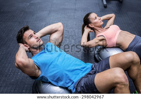 Muscular couple doing abdominal crunch on a bosu ball - stock photo