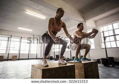 Muscular couple doing jumping squats in crossfit gym - stock photo
