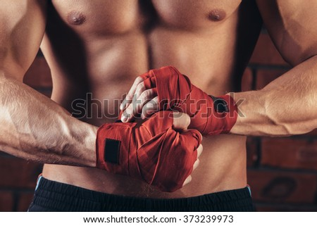 Muscular Fighter With Red Bandages against the background of a brick wall - stock photo
