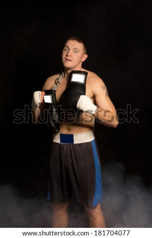 Muscular fit young boxer preparing for a fight standing in the darkness with his gloves slung round his neck and bandaged hands looking at the camera - stock photo