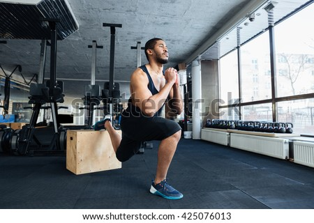 Muscular fitness man doing squats using wooden stand in the gym - stock photo