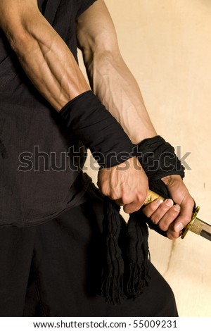 muscular forearms of a martial artist, samurai warrior with a natural wood background - stock photo