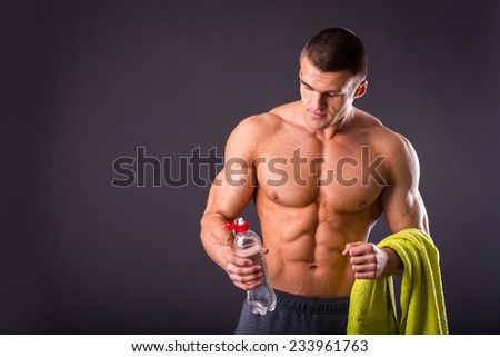 Muscular guy - bodybuilder posing on a gray background. Athletic man holding a bottle of water in hand, a towel around his neck. Sport, health, bodybuilding, strength, power - a concept sports. - stock photo