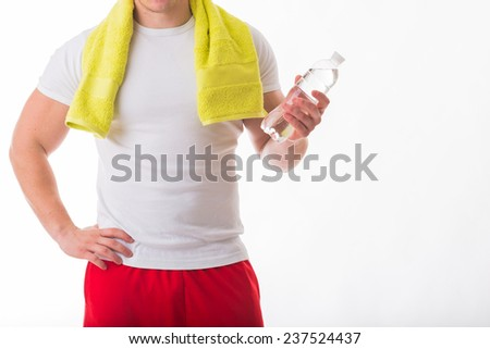 Muscular guy - bodybuilder posing on white background. Athletic man holding a bottle of water in hand, a towel around his neck. Sport, health, bodybuilding, strength, power - a concept sports. - stock photo