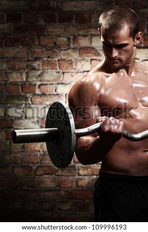 Muscular guy doing exercises with barbell against a brick wall - stock photo