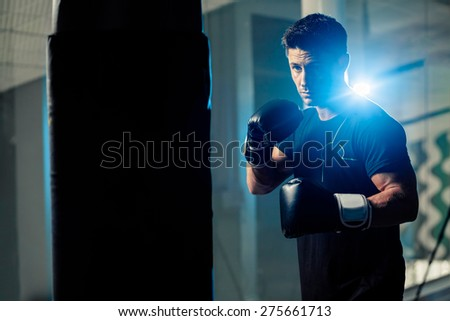 muscular handsome boxing man fighter with boxing bag - stock photo