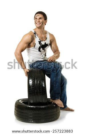 muscular handsome  guy hold rubber-tire and white,  on  white background, isolated - stock photo