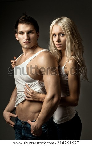 muscular handsome sexy guy with pretty woman, on dark blue  background - stock photo