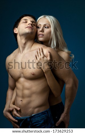 muscular handsome sexy guy with pretty woman, on dark blue  background, glamour  light - stock photo