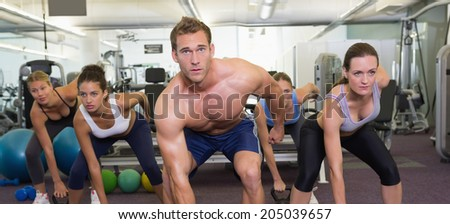 Muscular instructor leading kettlebell class at the gym - stock photo