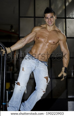 Muscular latino bodybuilder in jeans hanging from metal handle, showing ripped body - stock photo