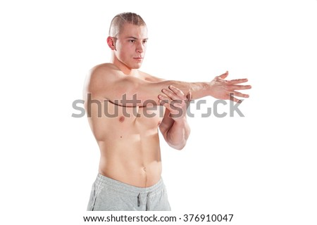 Muscular male bodybuilder stretching arms isolated on white - stock photo