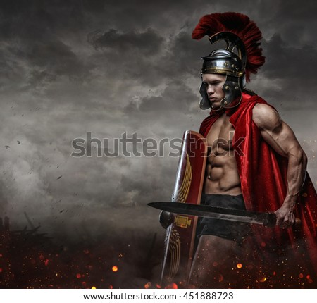 Muscular male in spartan costume holding sword and shield under stormy sky. - stock photo