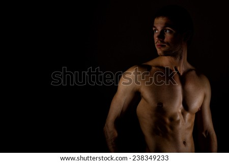 Muscular male model on black background. Place for your text. - stock photo