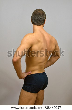 Muscular male model posing. Back view. - stock photo