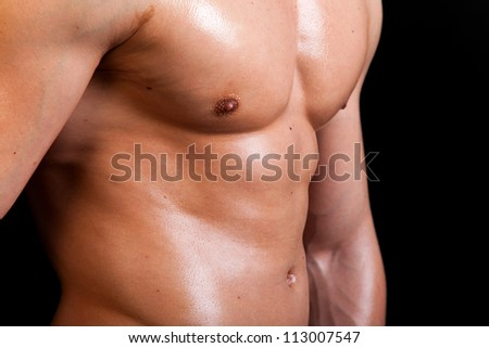 Muscular male torso on black background - stock photo