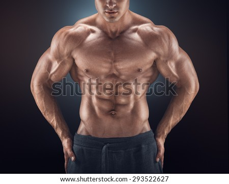 Muscular male torso. Young athletic man with great physique. Perfect fit, six pack, abs, shoulders, deltoids, biceps, triceps and chest. - stock photo