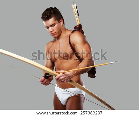 Muscular male with bow isolated on grey. - stock photo