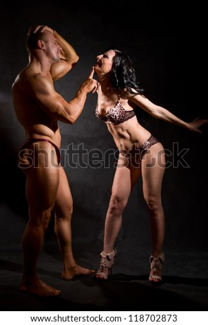 Muscular man and a woman posing in studio on dark background - stock photo