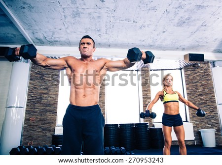 Muscular man and fit woman lifting dumbbells at gym - stock photo