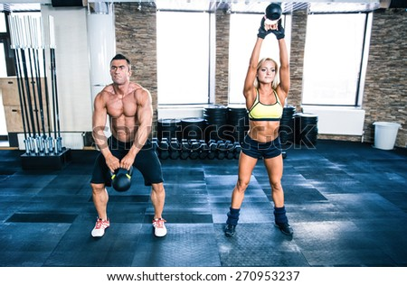 Muscular man and fit woman workout with kettle ball at gym - stock photo