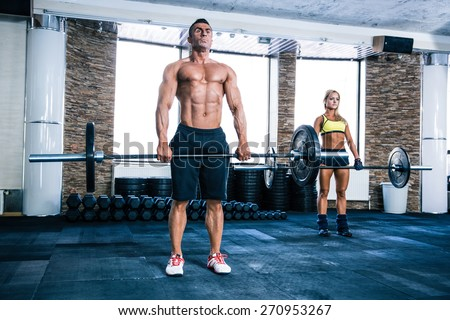 Muscular man and woman workout with barbell at gym - stock photo