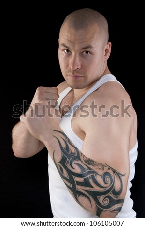 Muscular man body with a tattoo on his arm looking at the camera - stock photo