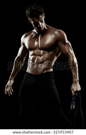 Muscular man bodybuilder. Man posing on a black background, shows his muscles. Bodybuilding, posing, black background, muscles - the concept of bodybuilding. - stock photo