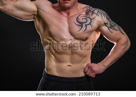 Muscular man bodybuilder with tattoos. Man posing on a black background, shows his muscles. Bodybuilding, posing, black background, muscles - the concept of bodybuilding. Article about bodybuilding. - stock photo