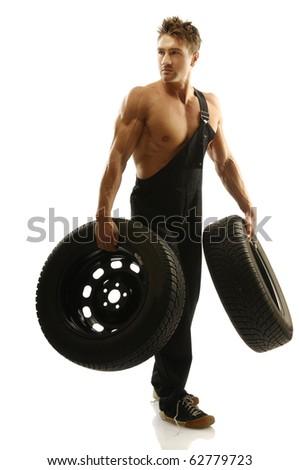 Muscular man carrying tires - stock photo