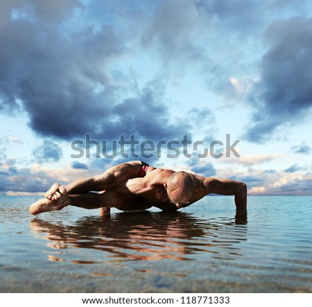 Muscular man doing eight arcs yoga pose into the water - stock photo