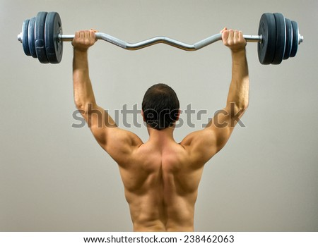 Muscular man doing exercises with barbell. Back view. - stock photo
