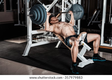 Muscular Man Doing Heavy Exercise. Athletic man pumping up muscles on bench press - stock photo