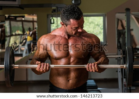 muscular man doing heavy weight exercise for biceps with dumbbell - stock photo