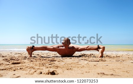 Muscular man doing stretching yoga pose at the sea beach - stock photo