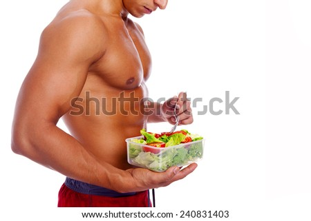Muscular man holding a bowl of fresh salad on a white background - stock photo