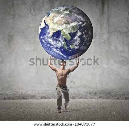 Muscular man holding the Earth in his hands [Elements of this image furnished by NASA] - stock photo