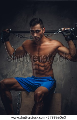 Muscular man in a blue shorts sitting on a wooden box and holding a hummer with chain on his shoulders. - stock photo