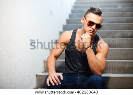 Muscular man in a shirt, jeans and sunglasses sitting on stairs. - stock photo