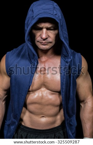 Muscular man in blue hood against black background - stock photo