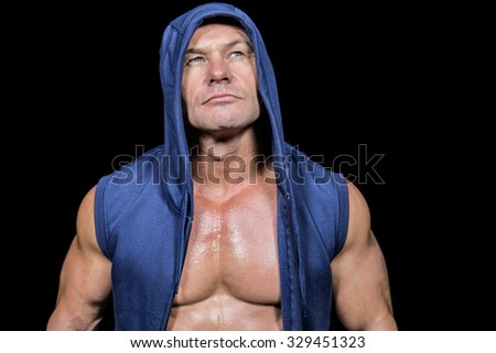 Muscular man in blue hood looking up against black background - stock photo